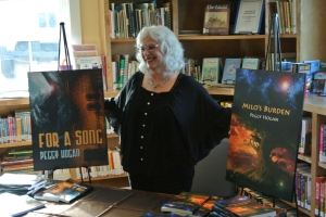 Peggy Hogan with the cover art of her two novels