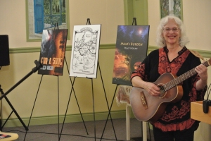 Peggy Hogan with the cover art of her two novels, and the illustrated map from Milo's Burden.